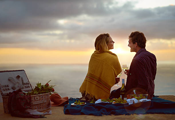 Mother nature setting the scene for love Shot of a young couple enjoying a romantic picnic at sunset date night romance stock pictures, royalty-free photos & images