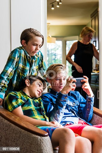 Three boys use a smartphone in the living room as a mother in the kitchen looks away and is not noticing what they are doing on-line.