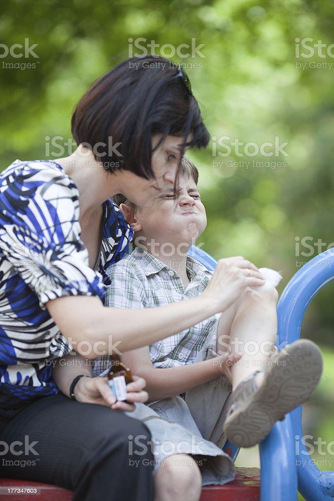 Mother nurturing her boys injured knee stock photo