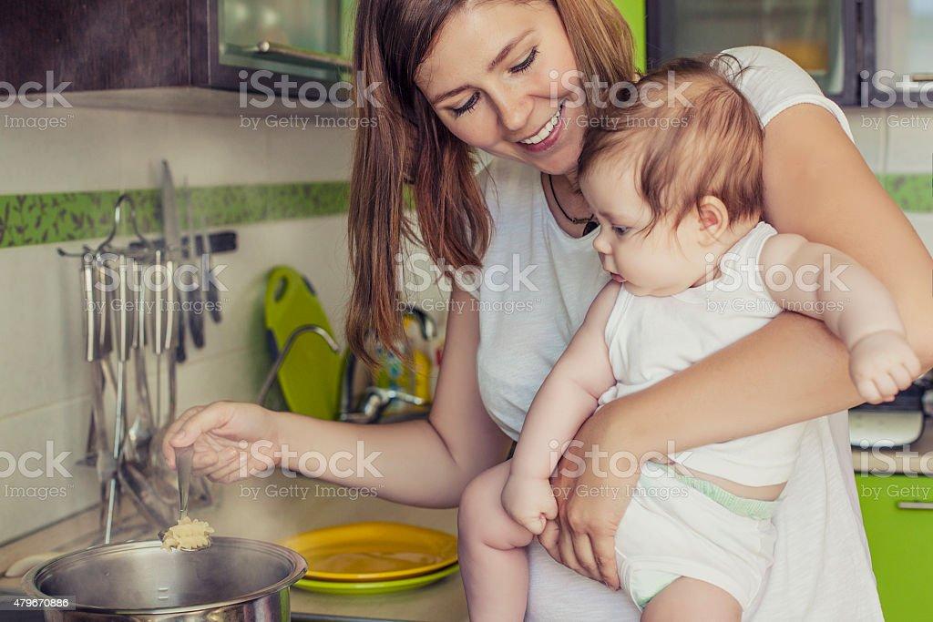 Madre de una mujer con un bebé prepara la comida - foto de stock