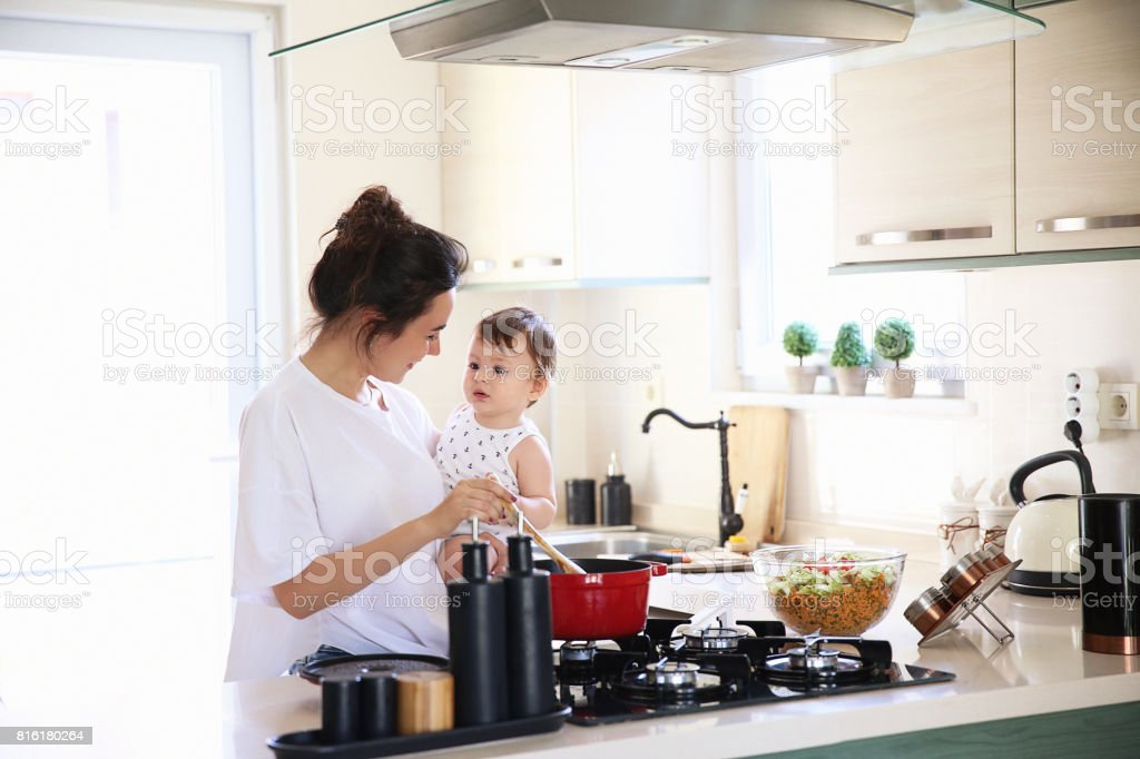 Mother of a woman with a baby cooks the food stock photo