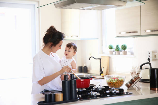 Mother of a woman with a baby cooks the food Kitchen, Cooking, Commercial Kitchen, Food, Pasta stove stock pictures, royalty-free photos & images