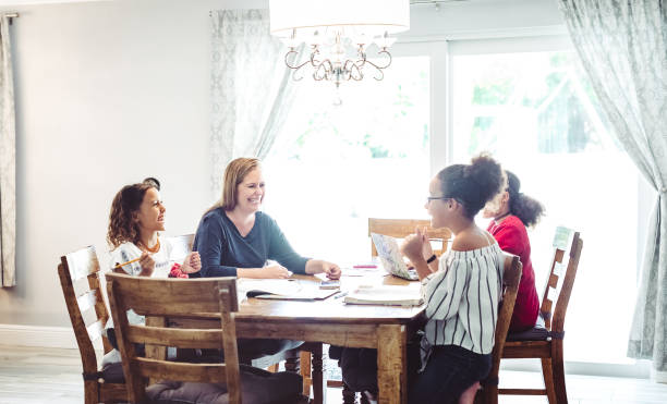 Mother of three supervises her school age daughters at home doing distance learning or schoolwork stock photo