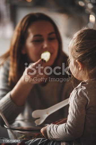 istock Mother offering slice of cucumber to her little daughter 1135709042