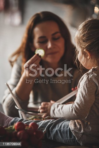 istock Mother offering slice of cucumber to her little daughter 1135709044