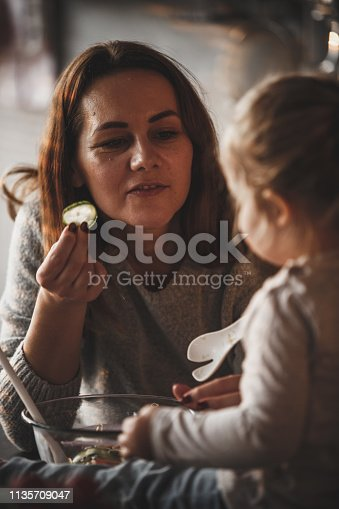 istock Mother offering slice of cucumber to her little daughter 1135709047