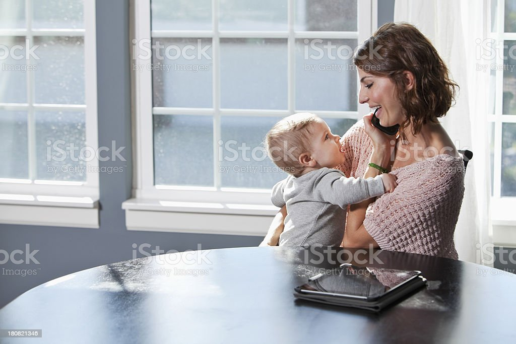 Mother on phone, holding baby stock photo