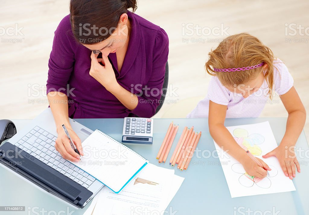 Mother on phone while writing notes by daughter drawing at desk royalty-free stock photo