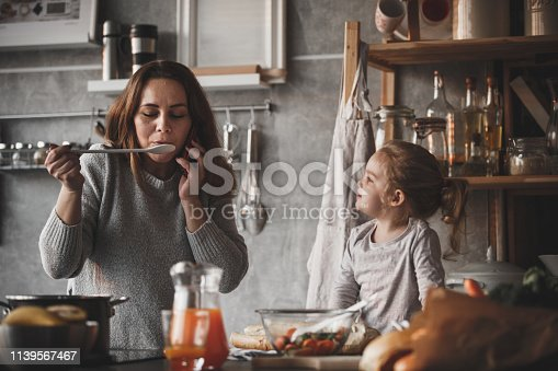 Mother and daughter cooking together, woman talking on the phone.