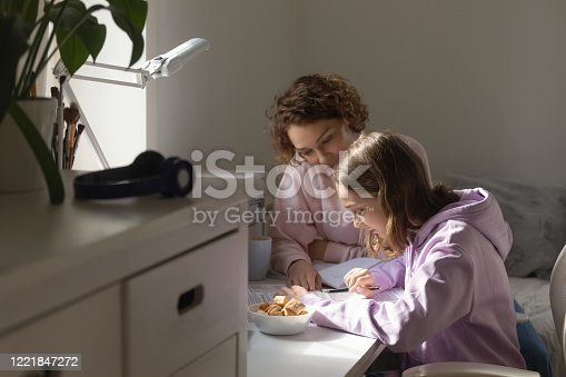 1051247474 istock photo Mother or tutor studying with teen daughter at home together 1221847272