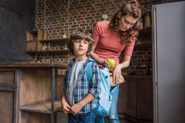 mother packing son before school stock photo