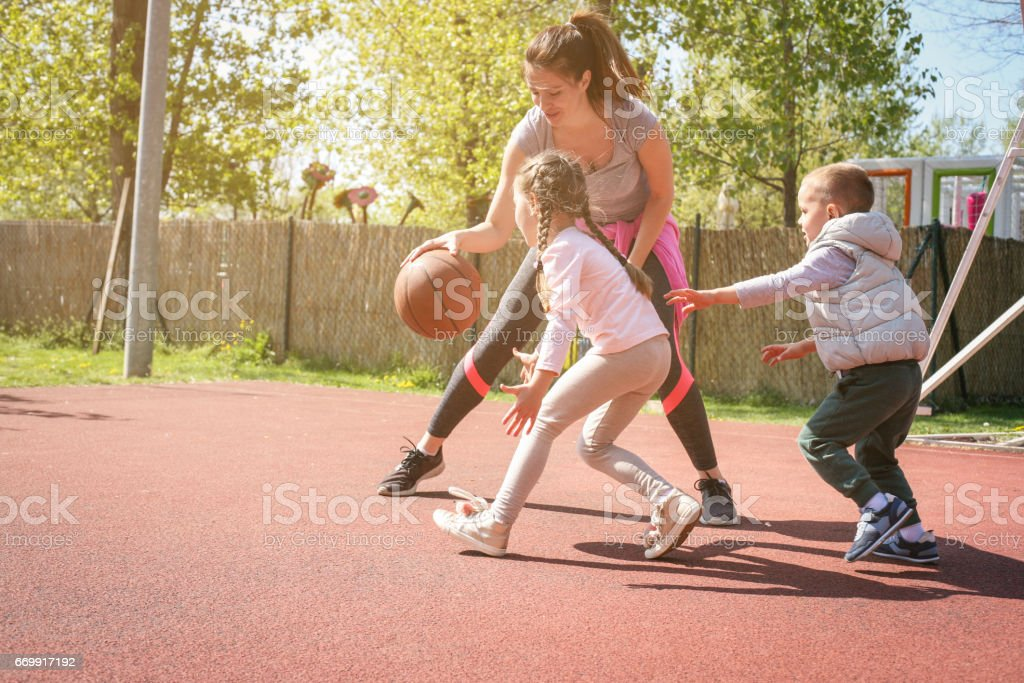 Mother paying basketball wit her children. stock photo