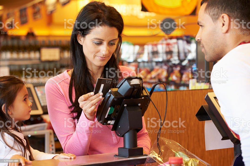 Mother Paying For Family Shopping At Checkout stock photo