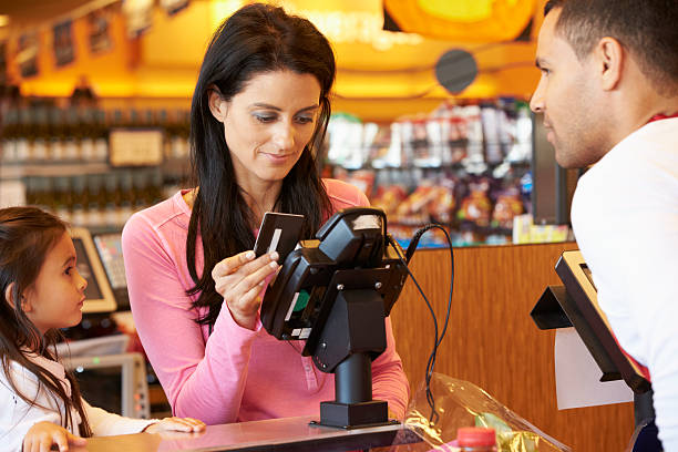 Mother Paying For Family Shopping At Checkout Mother Paying For Family Shopping At Checkout With Card smart card stock pictures, royalty-free photos & images