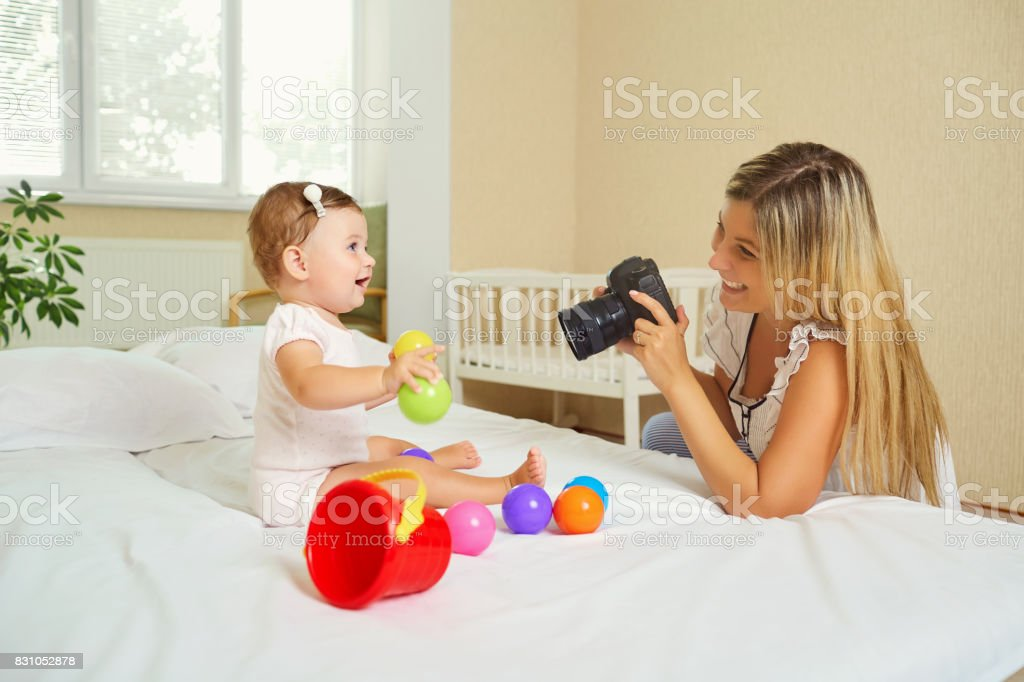 Mother  photographer photographing of her baby on camera. stock photo