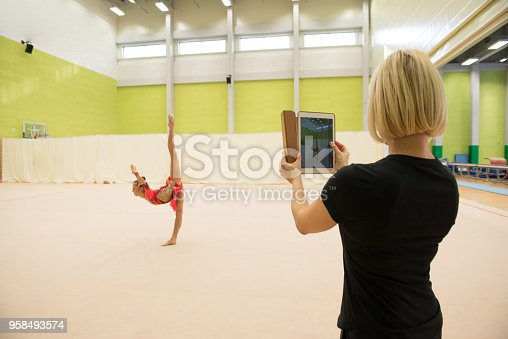istock Mother Photographing Her Daughter's Rhythmic Gymnastics Performance 958493574
