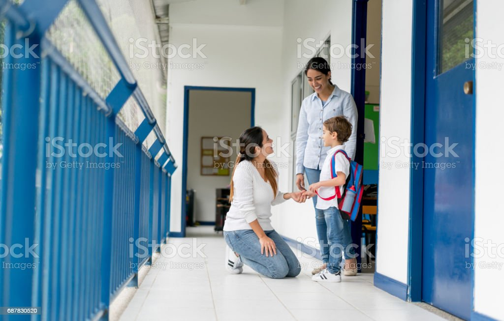 Mother picking up her kid from school and talking to the teacher stock photo