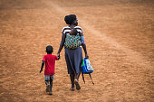 An Ugandan mother with her baby on back, has taken her son from school and is going home.