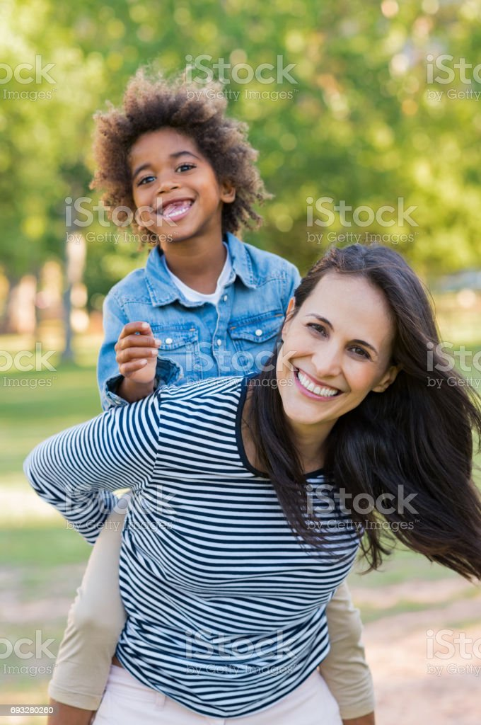 Mother piggybacking son at park stock photo