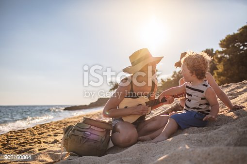 istock Mother Playing a guitar with her boys at the beach 902160864