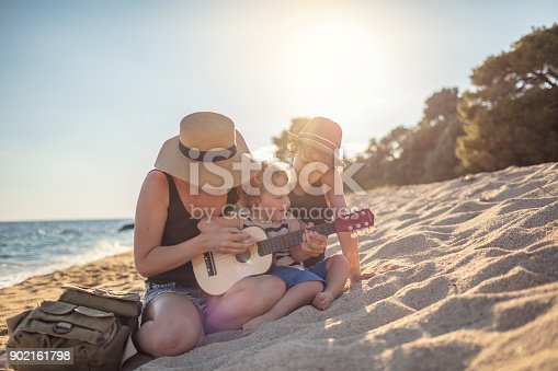656711080 istock photo Mother Playing a guitar with her boys at the beach 902161798