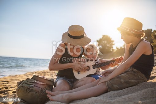 istock Mother Playing a guitar with her boys at the beach 902164418