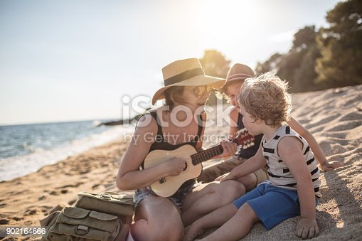 istock Mother Playing a guitar with her boys at the beach 902164666