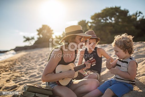 istock Mother Playing a guitar with her boys at the beach 902167710