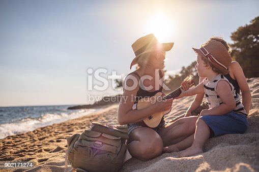 istock Mother Playing a guitar with her boys at the beach 902171274