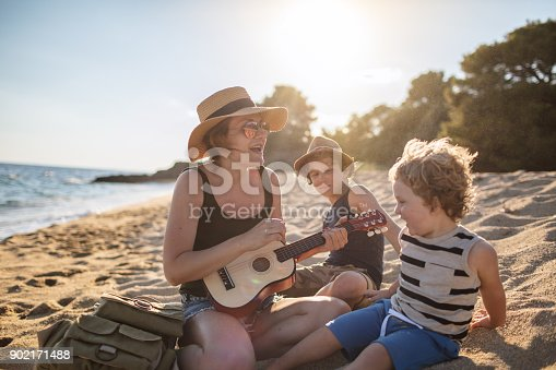 656711080 istock photo Mother Playing a guitar with her boys at the beach 902171488