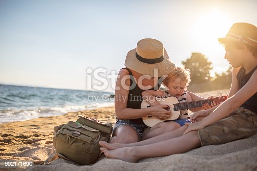 istock Mother Playing a guitar with her boys at the beach 902171690