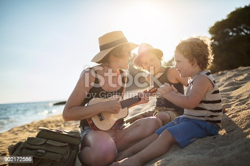 656711080 istock photo Mother Playing a guitar with her boys at the beach 902172586