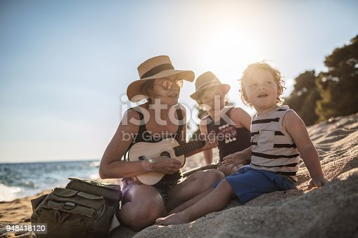 istock Mother Playing a guitar with her boys at the beach 948418120
