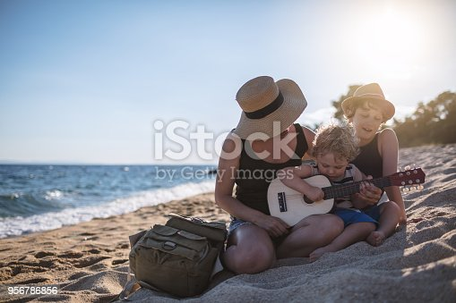 656711080 istock photo Mother Playing a guitar with her boys at the beach 956786856