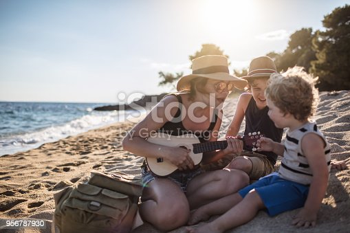 istock Mother Playing a guitar with her boys at the beach 956787930