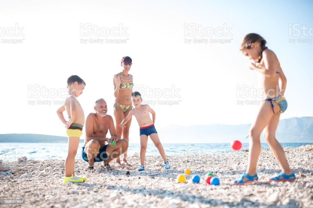 Mother Playing Boccia With Children On The Beach stock photo