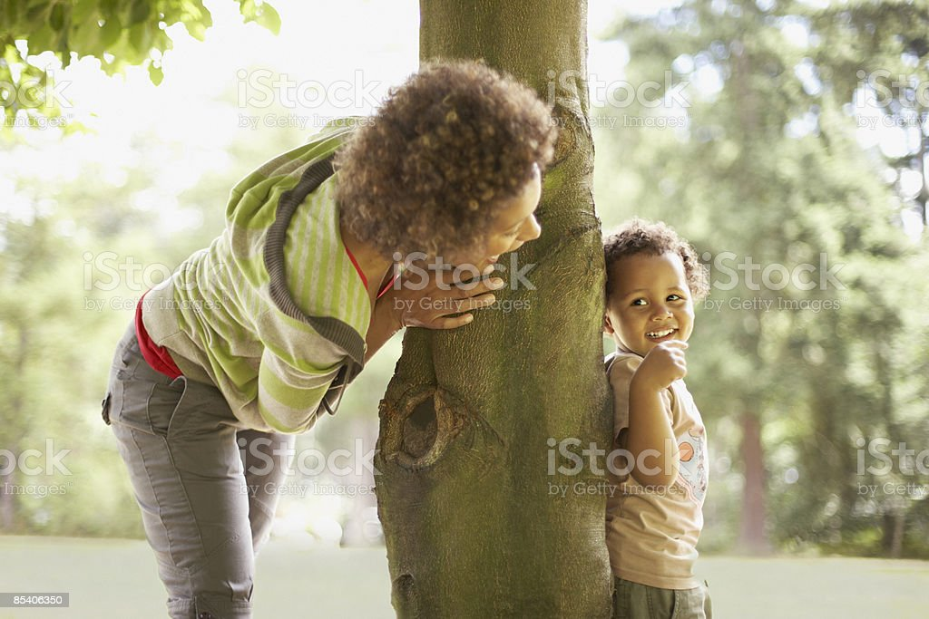Mother playing hide and seek with son stock photo