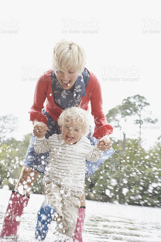 Mother playing in water with son stock photo