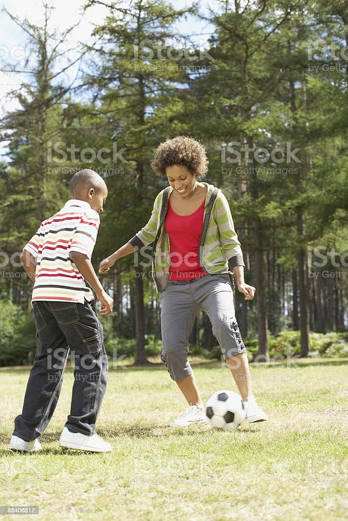 Mother playing soccer in park with son royalty-free stock photo