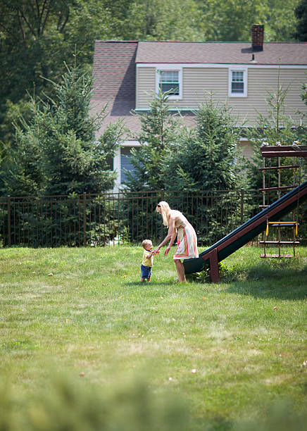 mother playing with baby boy in playground - distant stock photos and pictures