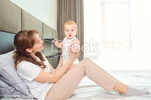 istock Mother playing with baby on the bed 1003318760
