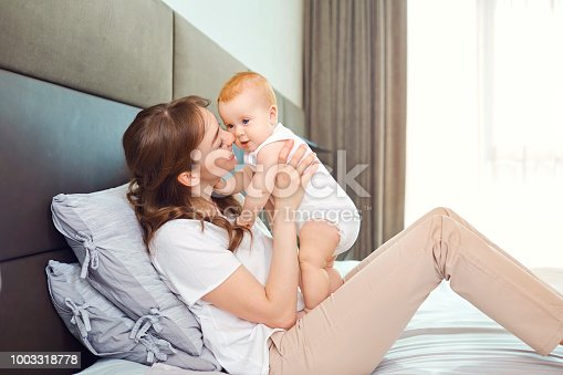 istock Mother playing with baby on the bed 1003318778