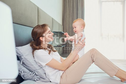 istock Mother playing with baby on the bed 936499690