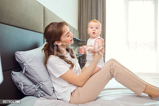 istock Mother playing with baby on the bed 937504786