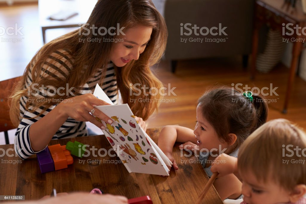 Mother Playing With Children On Table At Home stock photo