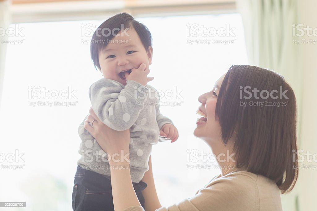 Mother playing with her baby girl at home stock photo