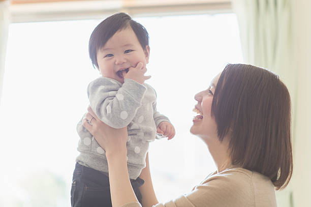 mother playing with her baby girl at home - 子供時代 ストックフォトと画像