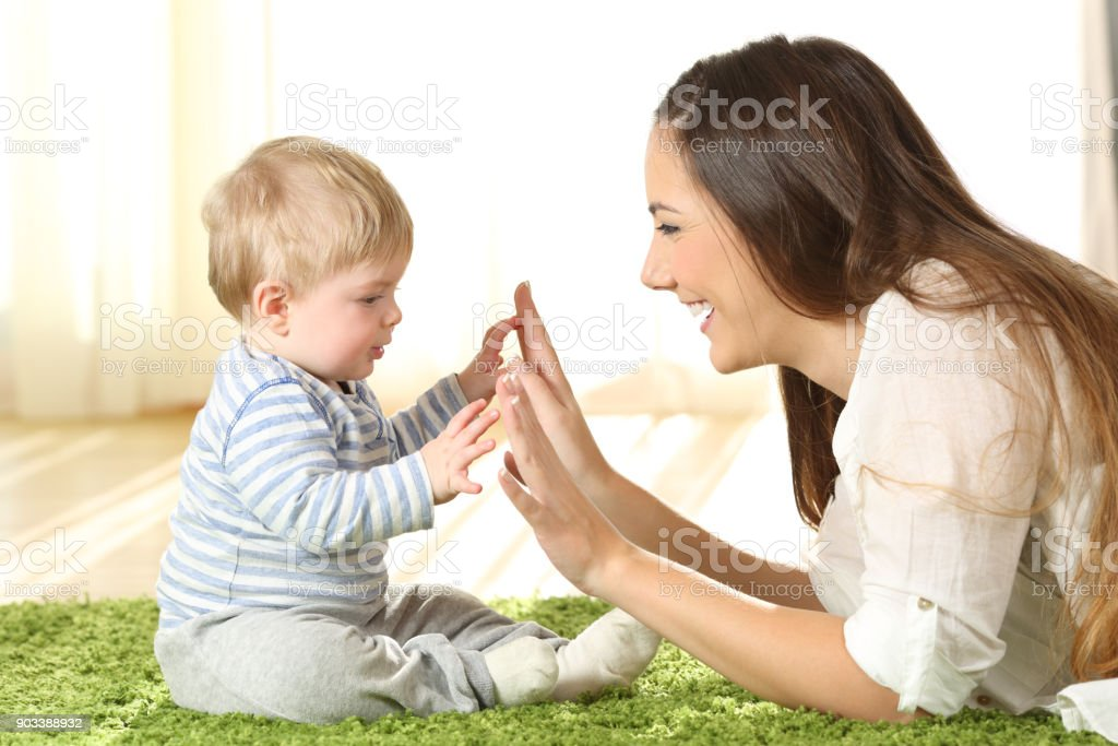 Mother playing with her baby on a carpet stock photo