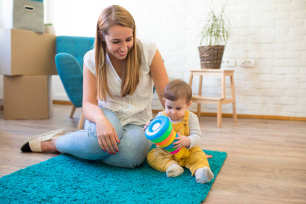 Mother playing with her baby on moving day stock photo