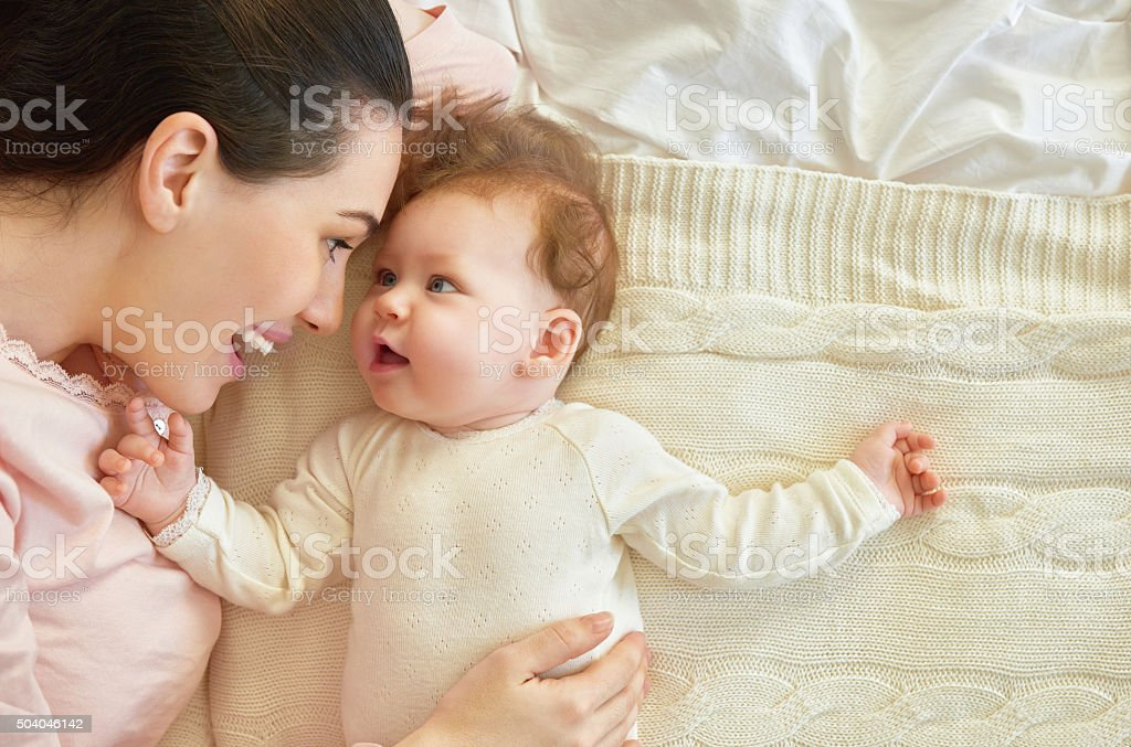 happy family. mother playing with her baby in the bedroom.
